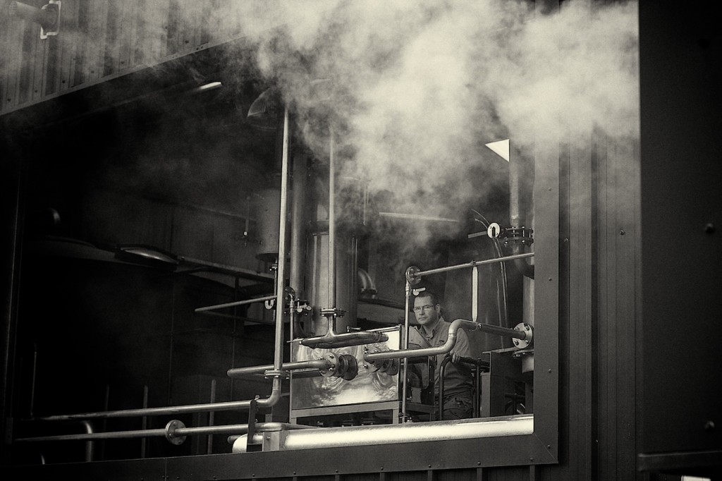 Black and white image of steam from inside Wolfburn distillery with manager Shane Fraser in background