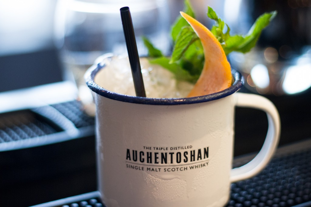 White tin mug with Auchentoshan on side, mint and orange in cup